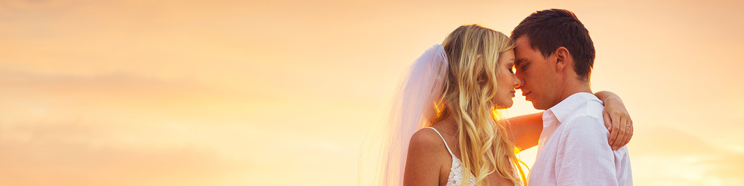 bride-and-groom-kissing-at-sunset-wide